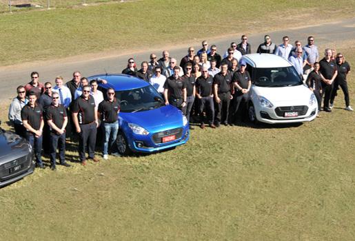 aerial shot of Suzuki QLD staff standing next to Suzuki Swifts