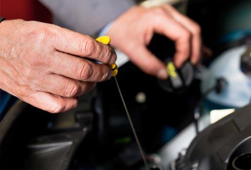 suzuki service technician checking oil level on dipstick